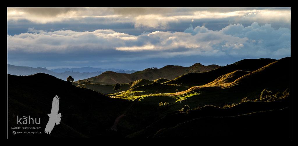Sunlight breaks through onto distant hills  -  L18